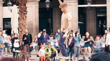tightrope : BARCELONA, SPAIN - APRIL, 16, 2017. Tightrope acrobat performing in the street. Balancing on a swaying strap. Stock Footage