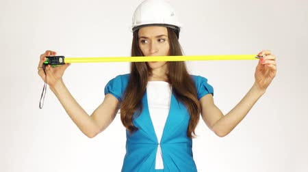 bant genişliği : Beautiful female construction engineer or architect in hard hat using measure tape against white background. 4K clip