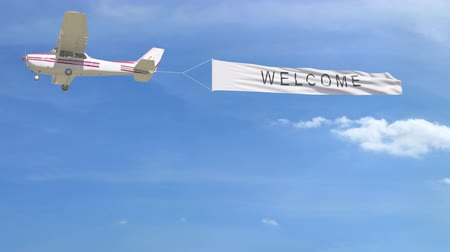 Small propeller airplane towing banner with WELCOME caption in the sky. 4K clip