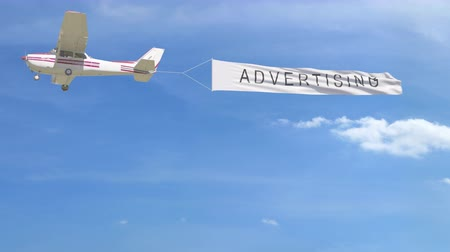 prapor : Small propeller airplane towing banner with ADVERTISING caption in the sky. 4K clip