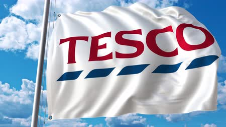 eixo : Waving flag with Tesco logo against moving clouds. 4K editorial animation