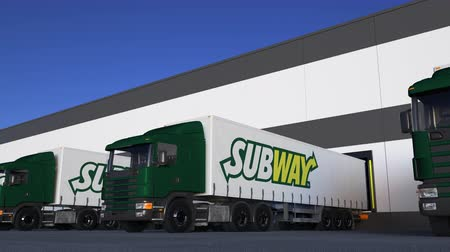 franczyza : Freight semi trucks with Subway logo loading or unloading at warehouse dock, seamless loop.