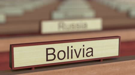 ábrázol : Bolivia name sign among different countries plaques at international organization. 3D rendering