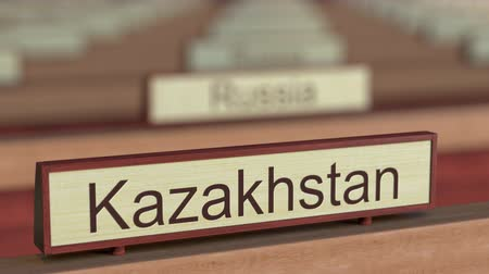 ábrázol : Kazakhstan name sign among different countries plaques at international organization. 3D rendering