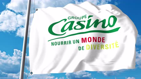 groupe : Waving flag with Groupe Casino logo against clouds and sky. 4K editorial animation Stock Footage