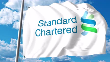 chartered : Waving flag with Standard Chartered logo against clouds and sky. Stock Footage