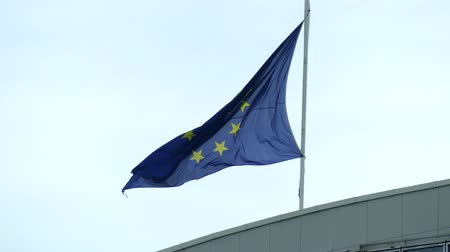 europeu : Waving worn flag of the European Union on the roof of a building Vídeos