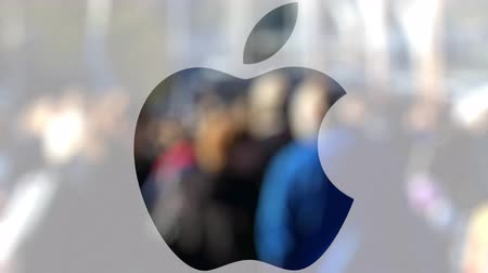 apple headquarter : Apple Inc. logo on a glass against blurred crowd on the steet. Editorial 3D rendering