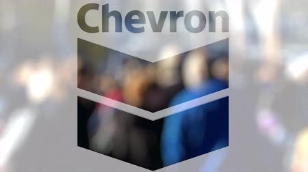 refining : Chevron Corporation logo on a glass against blurred crowd on the steet. Editorial 3D rendering