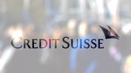 credit suisse : Credit Suisse Group logo on a glass against blurred crowd on the steet. Editorial 3D rendering Stock Footage