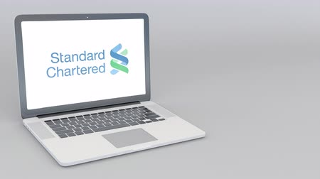 chartered : Opening and closing laptop with Standard Chartered plc logo. 4K editorial animation