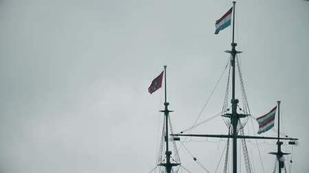 námořník : Waving flags of Netherlands and Amsterdam on the masts of an old ship memorial Dostupné videozáznamy