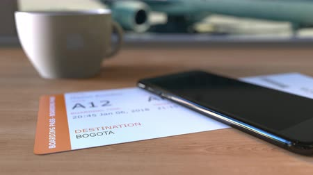 bogota : Boarding pass to Bogota and smartphone on the table in airport. Travelling to Colombia conceptual animation Stock Footage