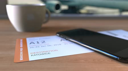 katowice : Boarding pass to Katowice and smartphone on the table in airport while travelling to Poland Wideo