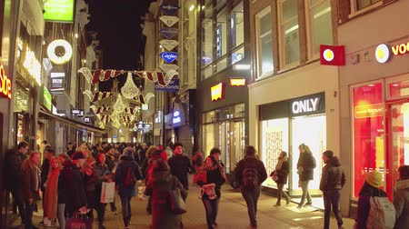 pedestrian only : AMSTERDAM, NETHERLANDS - DECEMBER 28, 2017. Crowded street and lit storefronts in the evening Stock Footage