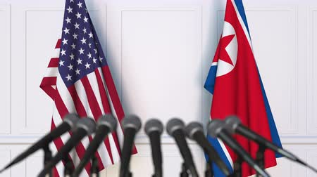 north korean flag : Flags of the USA and North Korea at international meeting or negotiations press conference Stock Footage