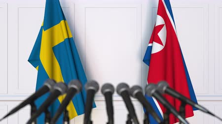 north korean flag : Flags of Sweden and North Korea at international meeting or negotiations press conference Stock Footage