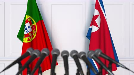 north korean flag : Flags of Portugal and North Korea at international meeting or negotiations press conference