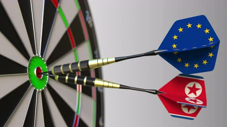 dprk : Flags of the European Union and North Korea on darts hitting bullseye of the target. International cooperation or competition conceptual animation