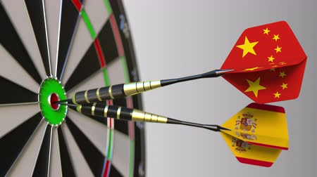 spaniard : Flags of China and Spain on darts hitting bullseye of the target. International cooperation or competition conceptual animation