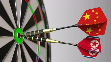 north korean flag : Flags of China and North Korea on darts hitting bullseye of the target. International cooperation or competition conceptual animation