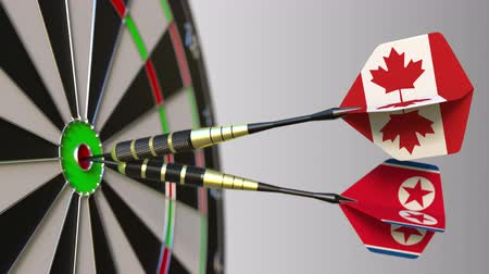 north korean flag : Flags of Canada and North Korea on darts hitting bullseye of the target. International cooperation or competition conceptual animation Stock Footage