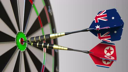 north korean flag : Flags of Australia and North Korea on darts hitting bullseye of the target. International cooperation or competition conceptual animation