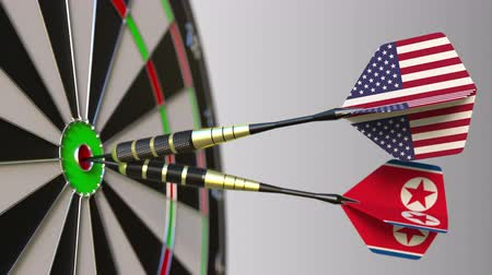 north korean flag : Flags of the USA and North Korea on darts hitting bullseye of the target. International cooperation or competition conceptual animation Stock Footage
