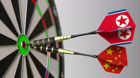 north korean flag : Flags of North Korea and China on darts hitting bullseye of the target. International cooperation or competition conceptual animation