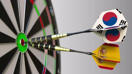 spaniard : Flags of South Korea and Spain on darts hitting bullseye of the target. International cooperation or competition conceptual animation