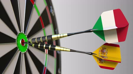 spaniard : Flags of Italy and Spain on darts hitting bullseye of the target. International cooperation or competition conceptual animation Stock Footage