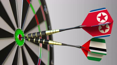 dprk : Flags of North Korea and the UAE on darts hitting bullseye of the target. International cooperation or competition conceptual animation Stock Footage