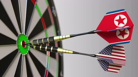 north korean flag : Flags of North Korea and the USA on darts hitting bullseye of the target. International cooperation or competition conceptual animation Stock Footage