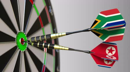 north korean flag : Flags of South Africa and North Korea on darts hitting bullseye of the target. International cooperation or competition conceptual animation Stock Footage