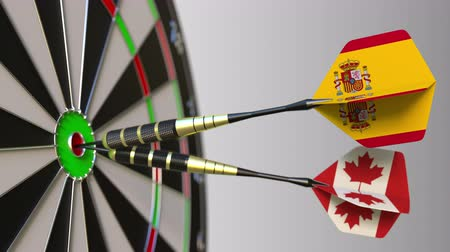 spaniard : Flags of Spain and Canada on darts hitting bullseye of the target. International cooperation or competition conceptual animation Stock Footage