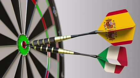 spaniard : Flags of Spain and Italy on darts hitting bullseye of the target. International cooperation or competition conceptual animation