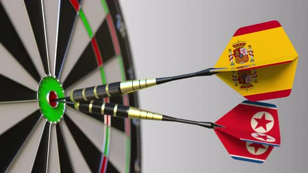 spaniard : Flags of Spain and North Korea on darts hitting bullseye of the target. International cooperation or competition conceptual animation