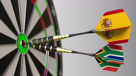 spaniard : Flags of Spain and South Africa on darts hitting bullseye of the target. International cooperation or competition conceptual animation Stock Footage