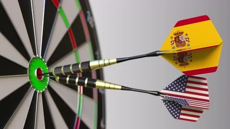 spaniard : Flags of Spain and the USA on darts hitting bullseye of the target. International cooperation or competition conceptual animation