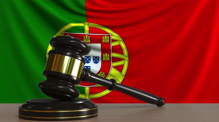 licit : Judges gavel and block against the flag of Portugal. Portuguese court conceptual animation