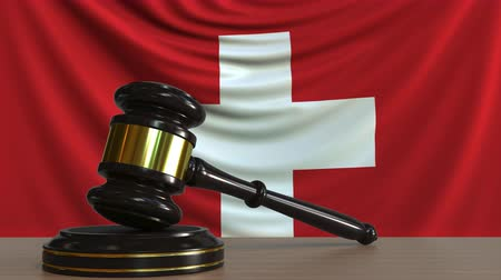 licit : Judges gavel and block against the flag of Switzerland. Swiss court conceptual animation