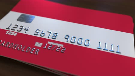 fraudulent : Plastic bank card featuring flag of Austria. Austrian banking system conceptual animation