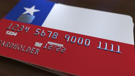 fraudulent : Plastic bank card featuring flag of Chile. Chilean banking system conceptual animation