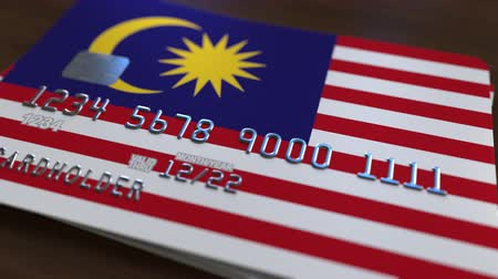 fraudulent : Plastic bank card featuring flag of Malaysia. Malaysian banking system conceptual animation Stock Footage