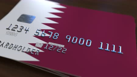 fraudulent : Plastic bank card featuring flag of Qatar. Qatari banking system conceptual animation Stock Footage