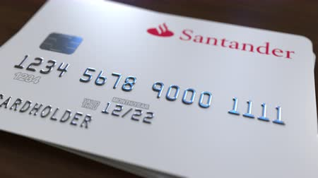 debit : Plastic card with logo of Santander Bank. Editorial conceptual 3D animation Stock Footage