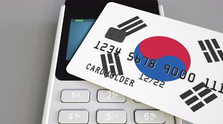 payment terminal : Payment or POS terminal with credit card featuring flag of South Korea. Korean retail commerce or banking system conceptual animation