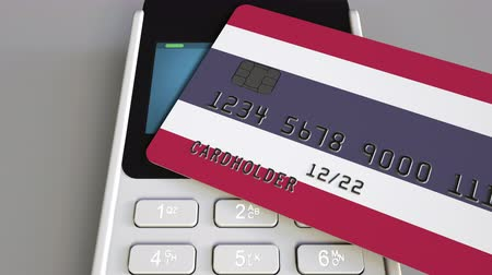 rachunek : Payment or POS terminal with credit card featuring flag of Thailand. Thai retail commerce or banking system conceptual animation