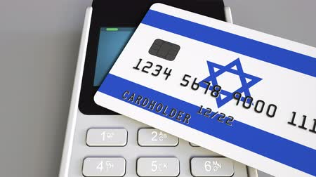 izrael : Payment or POS terminal with credit card featuring flag of Israel. Israeli retail commerce or banking system conceptual animation