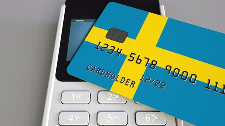 švédský : Payment or POS terminal with credit card featuring flag of Sweden. Swedish retail commerce or banking system conceptual animation